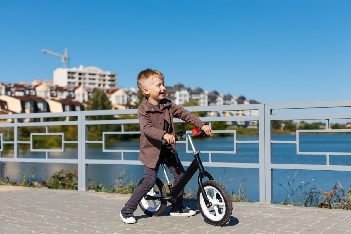 Happy four years old boy riding bicycle without pedals on the background of river and buildings. Sport concept. First balance bike for little children. Active and fun childhood outdoors