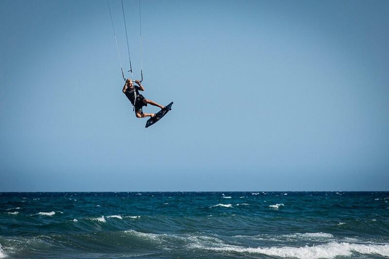 barbat practicand kitesurfing la mare