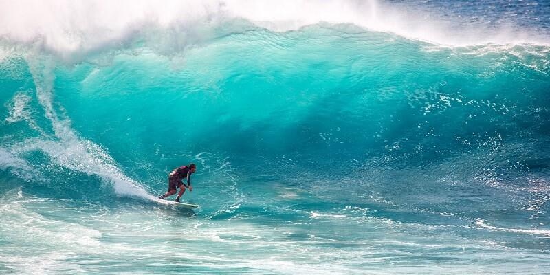 barbat practicand surfing pe valuri