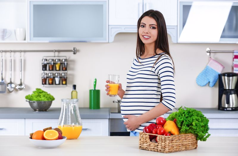 Pregnant,Woman,With,Glass,Of,Orange,Juice,In,The,Kitchen